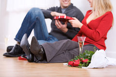 Valentine's: Couple Having Champagne and Candy. Fun Valentine's Day Holiday series with young Caucasian couple sitting around exchanging gifts Stock Photo