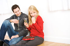 Valentine`s: Couple Sitting On Floor Eating Chocolate and Drinki Royalty Free Stock Photography