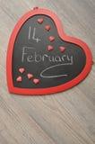 Valentine& x27; s-dag Ett bräde för hjärtaformsvart med 14 Februari Fotografering för Bildbyråer