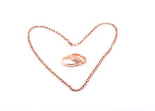 Valentine's Day. Heart from a gold chain and two wedding rings on a white background Royalty Free Stock Photos