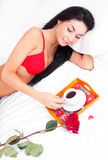 Valentine's day. Beautiful young brunette woman sleeping in bed at home on a Valentine's day with a tray with coffe and a rose standing near her Stock Images