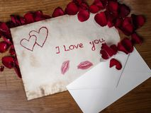 Valentine's Day. Composition of old valentines cards and envelopes with scattered rose petals on the wooden table stock images