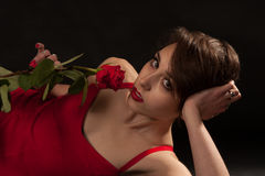 Valentine's Day. A young woman in a red dress is looking at you while holding a rose Stock Image