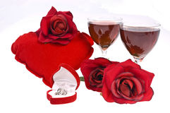 Valentine's day. Setup with two glasses of wine, one heart, roses and a gift Stock Photos