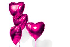 Valentine`s Day. Air balloons. Bunch of purple heart shaped helium balloons isolated on white Stock Image