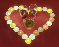 Valentine's Day background. Red romantic Valentine's Day composition with two glass of wine in the center of candle burn heart Royalty Free Stock Photos