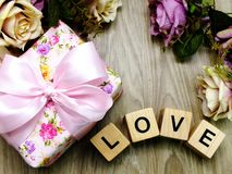 Valentine`s day background alphabet word love letter. Love word wooden block with artificial roses flowers decor stock image