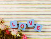 Valentine`s day background alphabet word love letter. Love word wooden block with artificial roses flowers decor stock photo