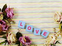 Valentine`s day background alphabet word love letter. Top view Love word wooden block with artificial roses flowers decor stock photography