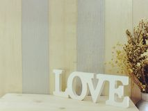 Valentine`s day background alphabet word love letter. S with dried flower with metal vase royalty free stock image
