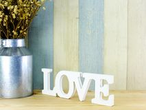 Valentine`s day background alphabet word love letters. With dried flower with metal vase stock photo