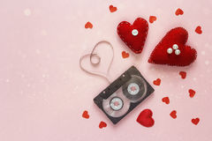 Valentine`s Day background with audio cassette tape in the shape. Of heart and red fabric hearts on pink background. Space for text Stock Photo