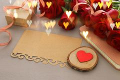 Valentine& x27;s day background. Beautiful bouquet of roses next to empty letter on wooden table. Stock Photo