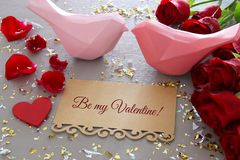 Valentine& x27;s day background. Beautiful bouquet of roses next to letter with text BE MY VALENTINES on wooden table. Royalty Free Stock Photo