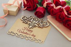 Valentine& x27;s day background. Beautiful bouquet of roses next to letter with text HAPPY VALENTINES DAY on wooden table. Stock Image