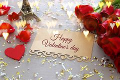 Valentine& x27;s day background. Beautiful bouquet of roses next to letter with text HAPPY VALENTINES DAY on wooden table. Stock Photography