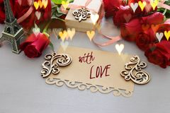 Valentine& x27;s day background. Beautiful bouquet of roses next to letter with text WITH LOVE on wooden table. Royalty Free Stock Photo