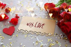 Valentine& x27;s day background. Beautiful bouquet of roses next to letter with text WITH LOVE on wooden table. Royalty Free Stock Photography