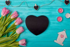 Valentine`s Day background with bouquet of tulips and valentine in the shape of a heart and a candle. Valentine`s Day royalty free stock image