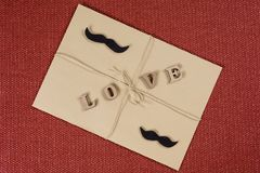Valentine`s Day background, brown kraft envelope with the word love, with kraft rope. Couple man-man. Valentine`s Day background, brown kraft envelope with the Royalty Free Stock Images