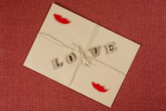 Valentine`s Day background, brown kraft envelope with the word love, with kraft rope. Couple woman-woman. Valentine`s Day background, brown kraft envelope with Stock Images