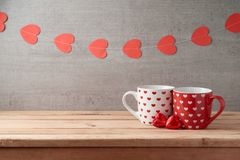 Valentine`s day background with coffee cups, heart shape chocolate and garland. On wooden table stock images