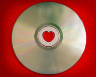 Valentine`s day background - colorful CD disk with heart shape in the central part. Red Valentine`s day background - colorful CD disk with heart shape in the Royalty Free Stock Photography