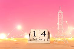 Valentine's day background. Eiffel tower and vintage wooden calendar with 14th february date over table and pink bakground. stock image