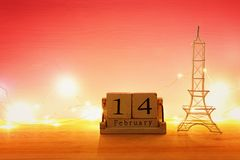 Valentine's day background. Eiffel tower and vintage wooden calendar with 14th february date over table and red bakground. royalty free stock image