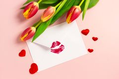 Valentine`s day background. Envelope with red lipstick kiss, hearts and tulips on pink. stock images