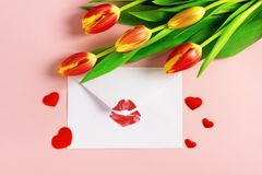 Valentine`s day background. Envelope with red lipstick kiss, hearts and tulips on pink. stock image