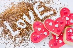 Valentine`s Day background - gold sprinkle love and heart shaped. Cookie on a white background Stock Photos