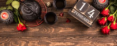Valentine`s day background. Valentine`s day background with green tea, black teapot, candles, roses and wooden calendar. Valentines day concept. Top view royalty free stock photo