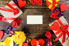 Valentine`s day background with greetings card,  hearts decorations and small gifts on wooden table. Top view with copy space. Copy paste Royalty Free Stock Photos