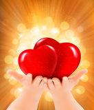 Valentine`s day background. Hands holding two red hearts Stock Photography