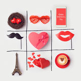 Valentine`s day background with heart shape and party accessories. Tic Tac Toe game concept. View from above. Stock Image