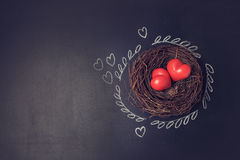Valentine's day background with hearts in bird nest over chalkboard. Royalty Free Stock Photo