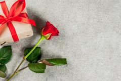Valentine`s day background. Holiday  background, Valentine`s day. Bouquet of red roses, tie with a red ribbon, with wrapped gift box and red candle. On a gray Stock Images