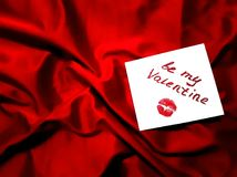 Valentine`s day background with love card on luxury red satin. Love note with words be my valentine and lip imprint on red crumbled satin. Card for Valentine`s Stock Image
