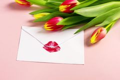 Valentine`s day background. Envelope with red lipstick kiss and tulips on pink. stock photo
