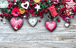 Valentine`s Day Background with love themed elements like cotton and paper hearts. Flowers, berries, oranges and other decorations. Wooden old parquet on the Royalty Free Stock Image