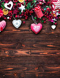 Valentine`s Day Background with love themed elements like cotton and paper hearts. Flowers, berries, oranges and other decorations. Wooden old parquet on the Stock Photos