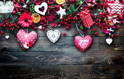 Valentine`s Day Background with love themed elements like cotton and paper hearts. Flowers, berries, oranges and other decorations. Wooden old parquet on the Royalty Free Stock Images