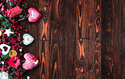 Valentine`s Day Background with love themed elements like cotton and paper hearts. Flowers, berries, oranges and other decorations. Wooden old parquet on the Stock Image