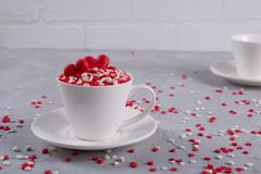 Valentine`s Day background . Many little colorful sprinkles hearts in a cup. Royalty Free Stock Photos