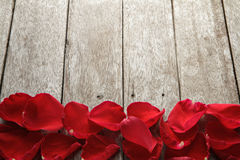 Valentine' s day background with petals of rose on wooden. Royalty Free Stock Images
