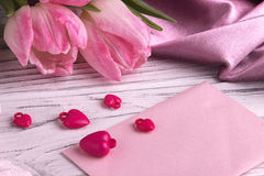 Valentine`s day background with pink tulip flowers red hearts shape sign on white pink envelope on white wooden background. stock image