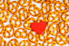 Valentine's day background pretzels pattern and red heart. Royalty Free Stock Photo