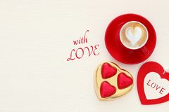 Valentine& x27;s day background. red cup of coffee with heart shape foam and chocolate. Top view image. Stock Images