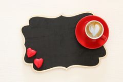 Valentine& x27;s day background. red cup of coffee with heart shape foam and chocolate. Top view image. Valentine& x27;s day background. red cup of coffee with stock images